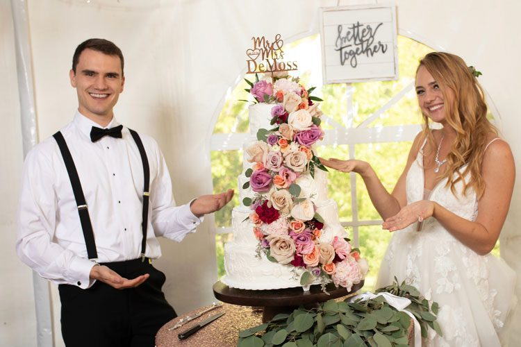 bride and groom about to cut wedding cake with flowers